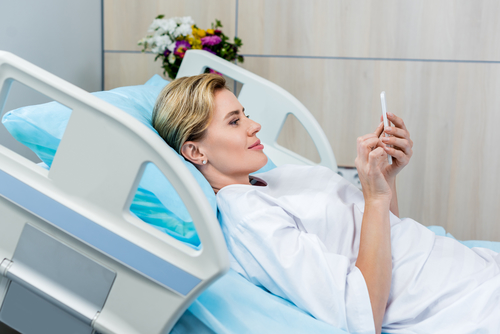 Mulher na cama de hospital assistindo culto ao vivo no celular
