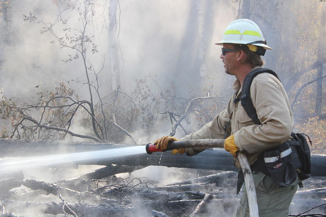 Engine Crewmember Sprays Hotspot. Photo: Mike McMillan - DNR