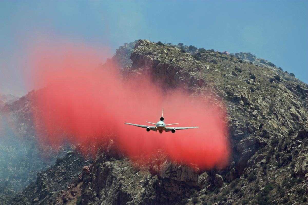 A rugged landscape of desert hillside is the background for a picture of a very large airtanker dropping a large load of bright pink fire retardant.