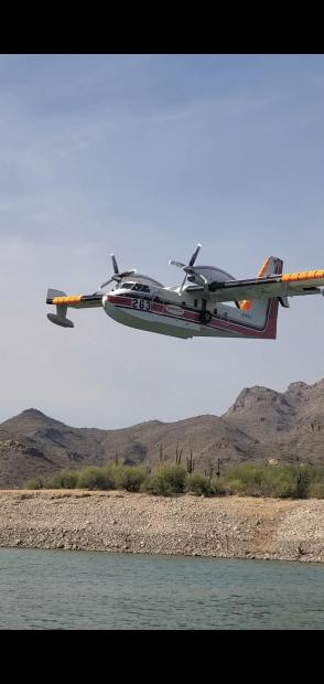Water scooping aircraft working on the West side of the fire