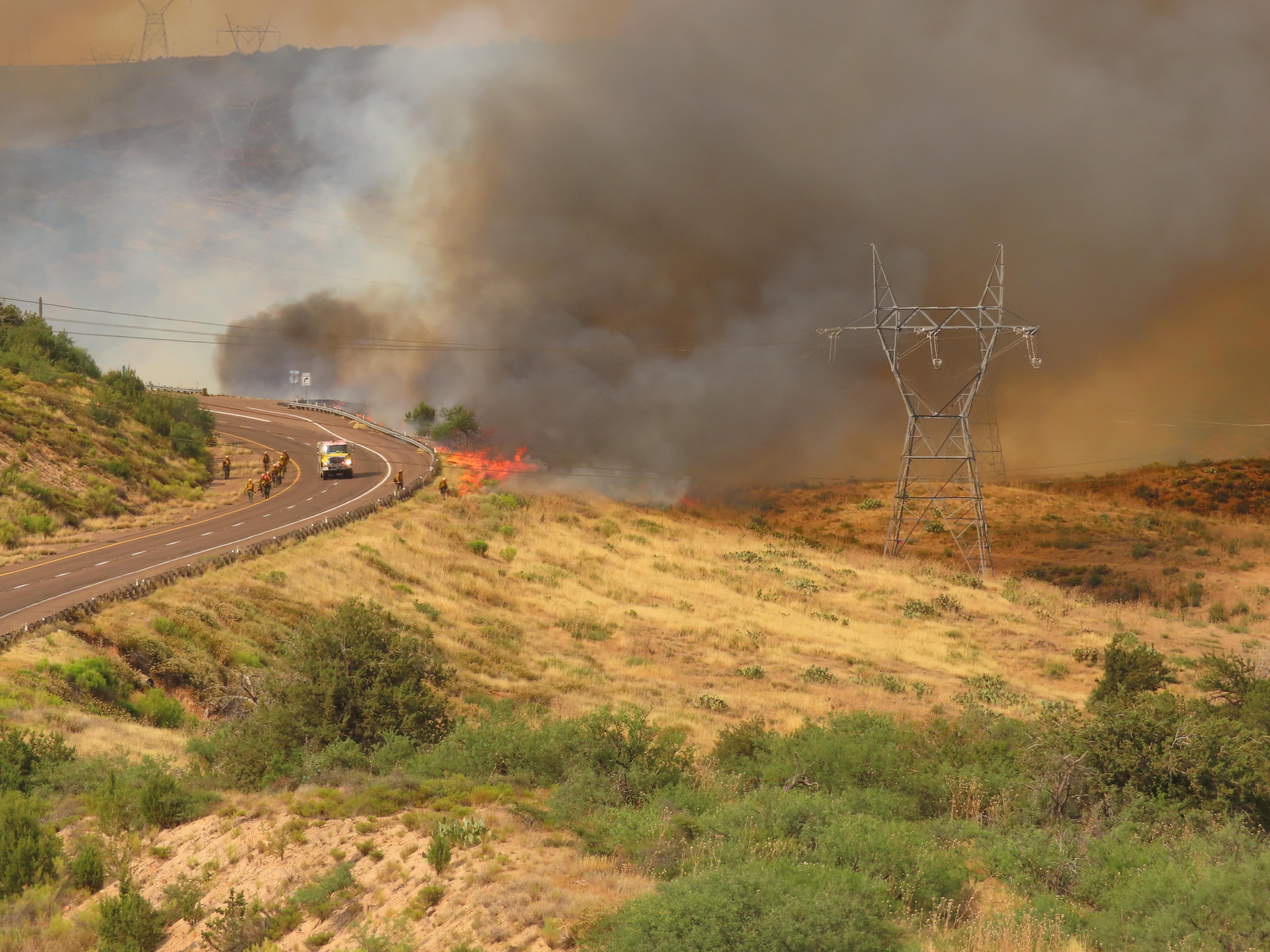 Firefighters work to contain the Bush Fire along the highway on the Tonto National Forest.