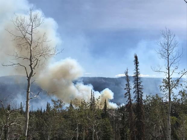 Unburned aspen and mixed conifer are visible in the foreground, with smoke rising behind a rocky ridge in the near distance.