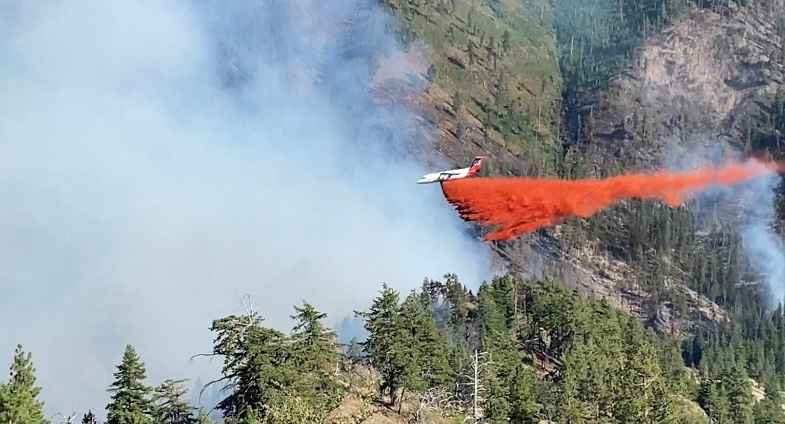 A plane drops a load of red retardant across a forested mountainside.