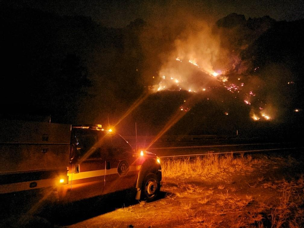 Fire engine and patches of flame in scrubland at night.