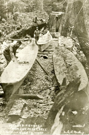 Carvers making canoes from a tree