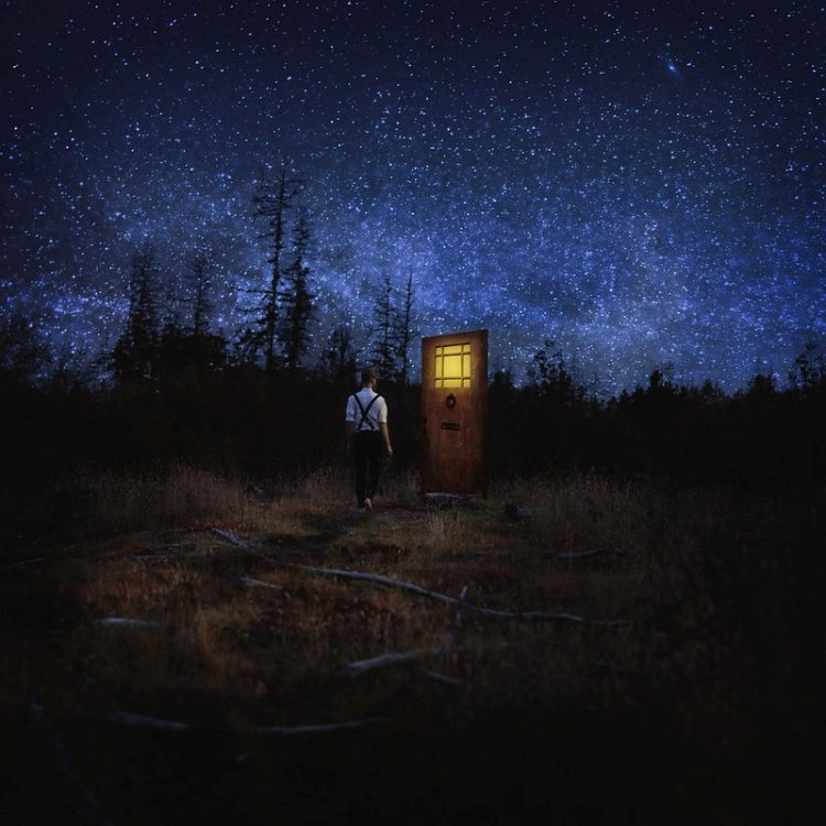 Young man approaches lighted door in field at night.