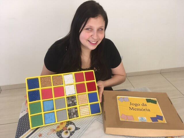 Jogo da Memória para Crianças com Deficiência Visual: Foto da professora com a caixa do brinquedo.
