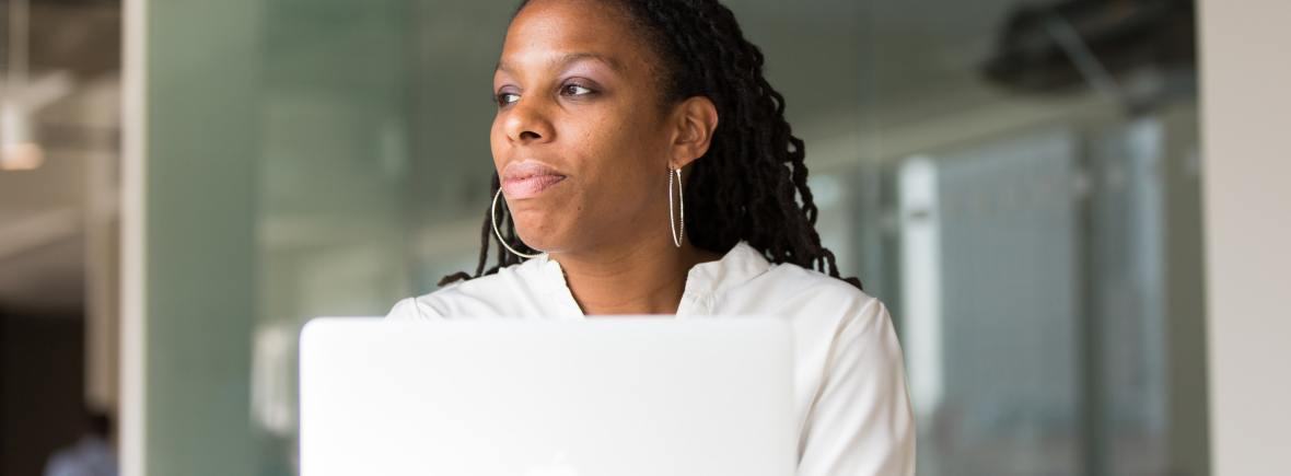 Women with brown skin and long hair reflecting in front of a laptop computer.
