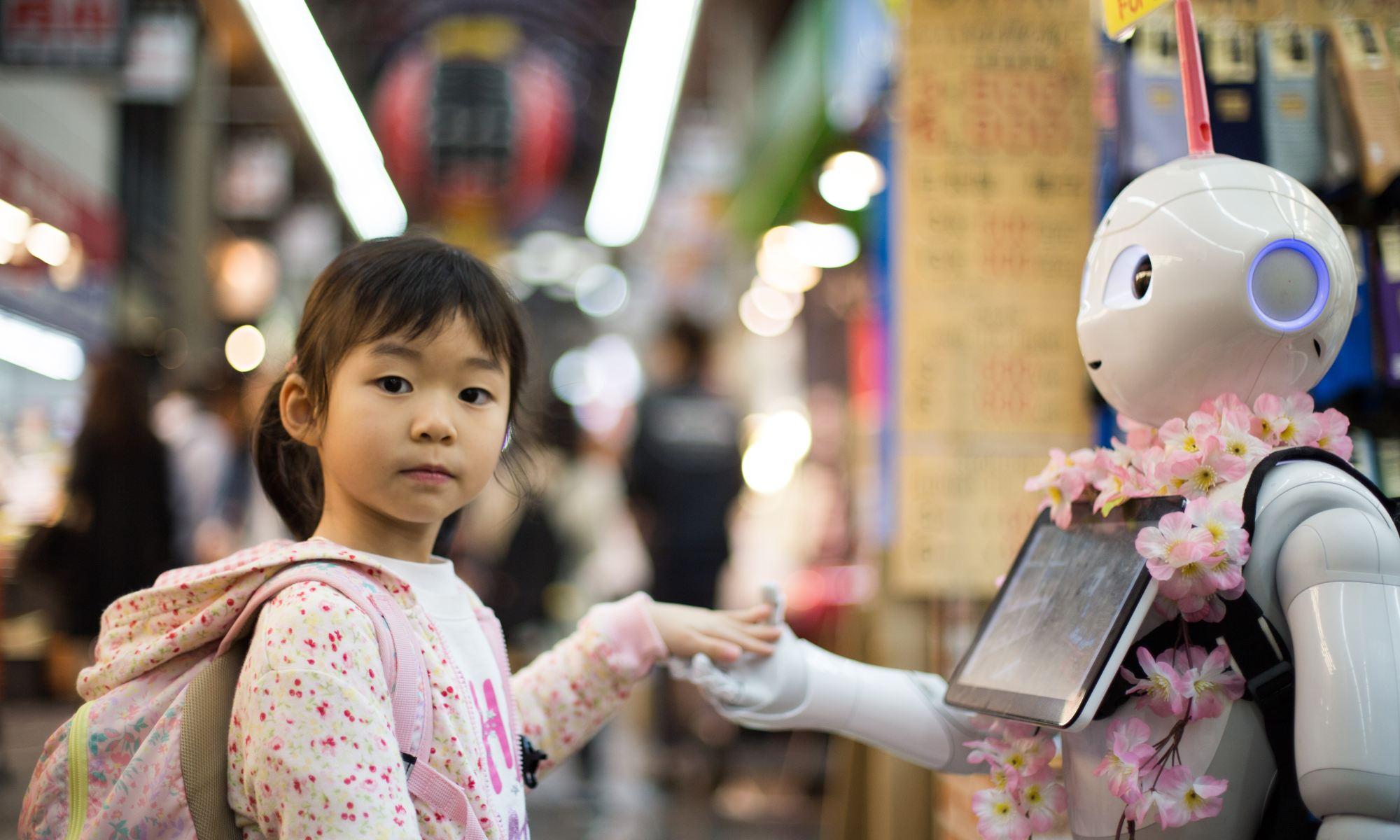 Niña y Robot dándose la mano.