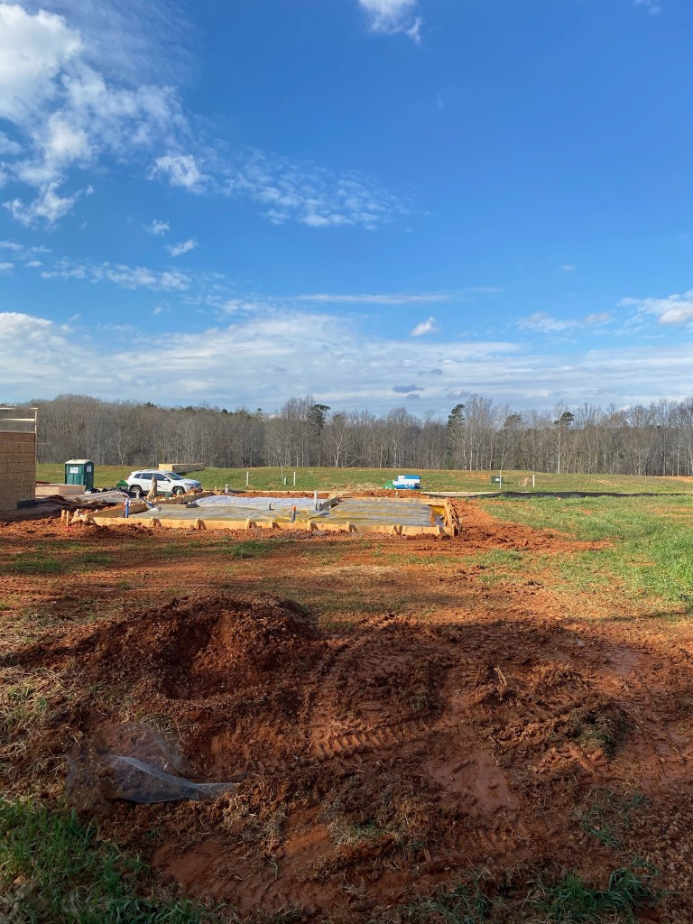 slab of foundation in the dirt with blue sky and tree line in background