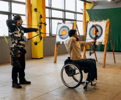 two peopl shooting arrows at a target, one is in wheel chair