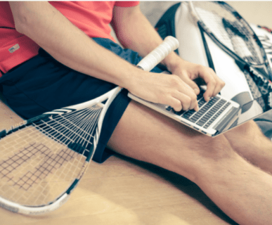 man uses laptop while holding a squash racquet