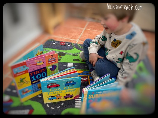 Child with three books on transport themed rug eyfs