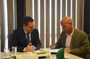Rogério Zardo assina o termo de posse. À esquerda, o presidente do Incra, Leonardo Góes