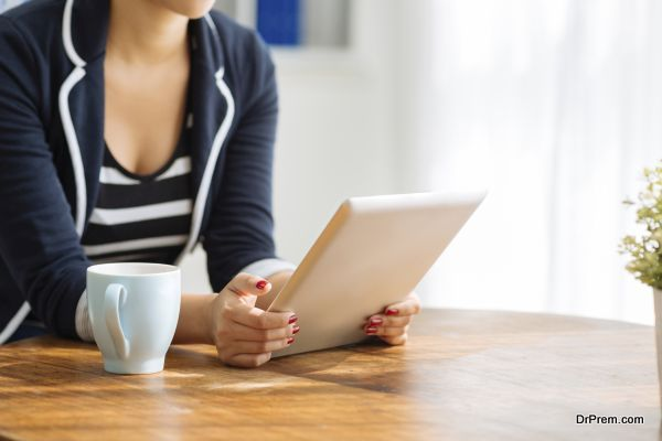 Cropped image of woman using digital tablet while drinking tea