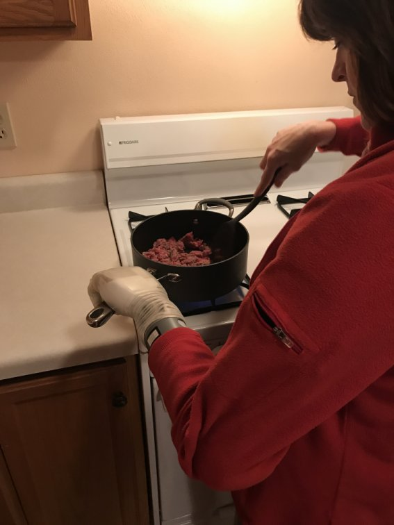 Carrie cooking, using the Luke Arm to hold pot