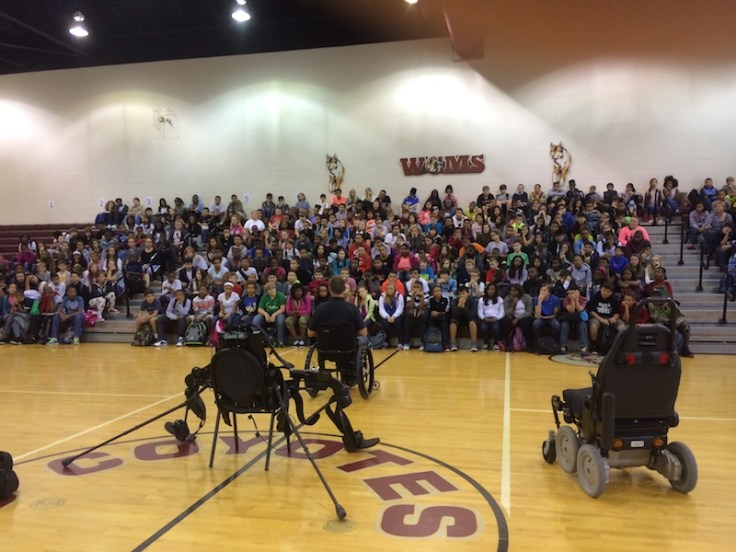 Gary Linfoot talking to student audience in gym with view of equipment
