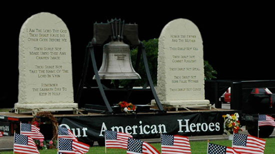 Photo of bell, gravestones and flags honoring American heroes