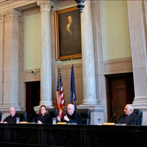 In this Thursday, April 12, 2018, photo, Justice Andrew M. Mead, third from right, asks a question during a hearing in the Maine Supreme Judicial Court on whether ranked-choice voting can be used in Maine's June 12th primary, in Portland, Maine.  The system lets voters to rank candidates on the ballot in order of preference. (AP Photo/Robert F. Bukaty)