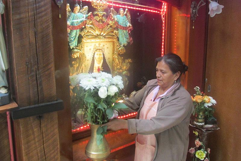 María de Lourdes arreglando las flores en el altar