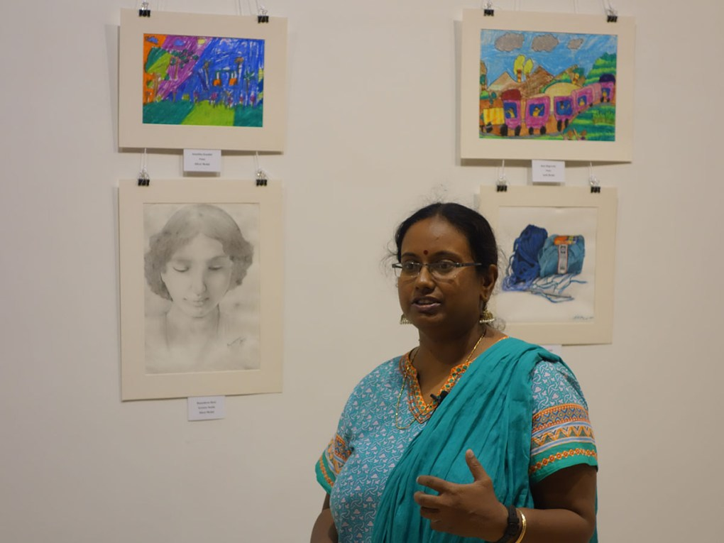 Art teacher Nivedita Datta with painting of her student Anushka Kamble at Khula Aasmaan art exhibition of medal winning artworks
