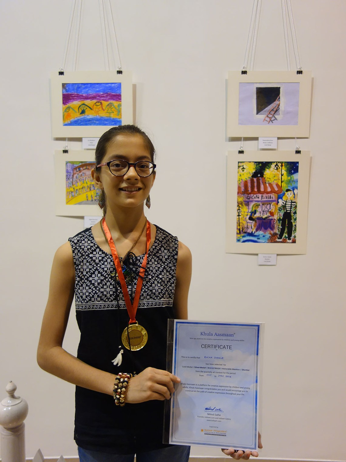 Rucha Damle with her medal and painting in the background at Khula Aasmaan art exhibition of medal winning artworks at Mumbai - October 2017. Rucha's video is part of videos of medal winning children.