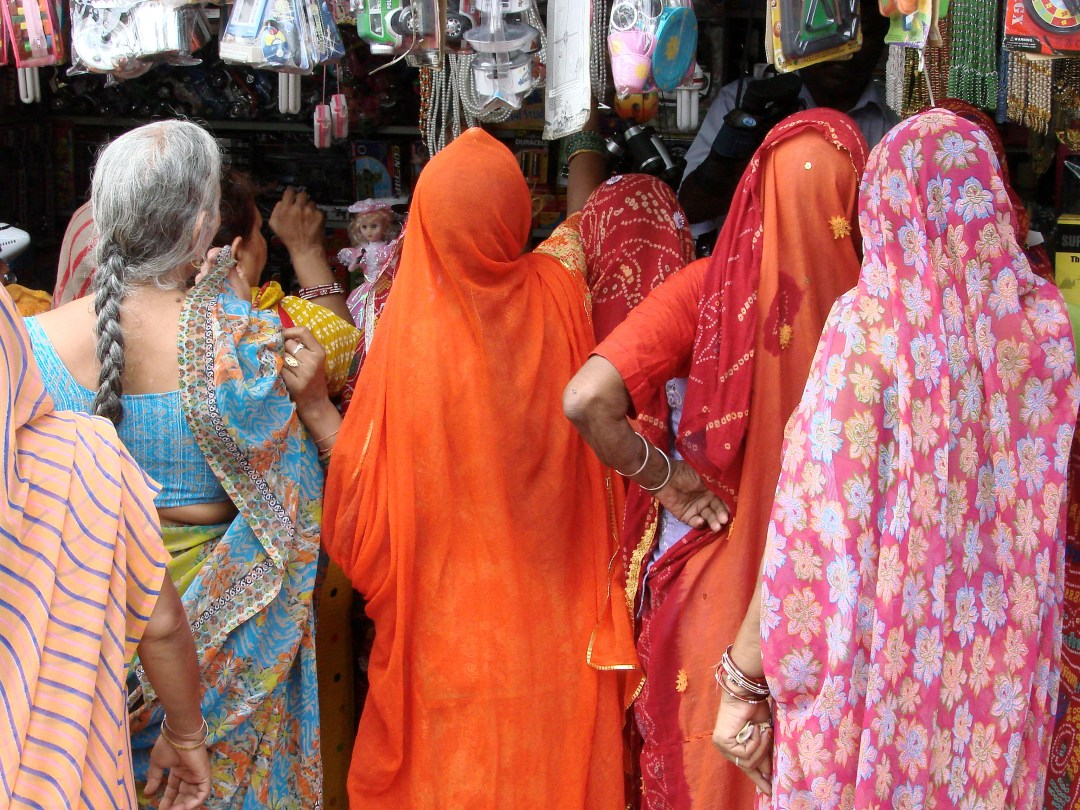 Women line the streets of a bazaar in their colorful saris