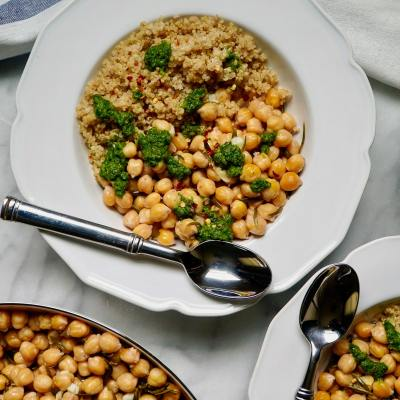 Garbanzo beans with quinoa and chimichurri sauce in white bowls with linen towels