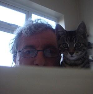 A photo of Martin Pallot and his kitten peeking over a sofa