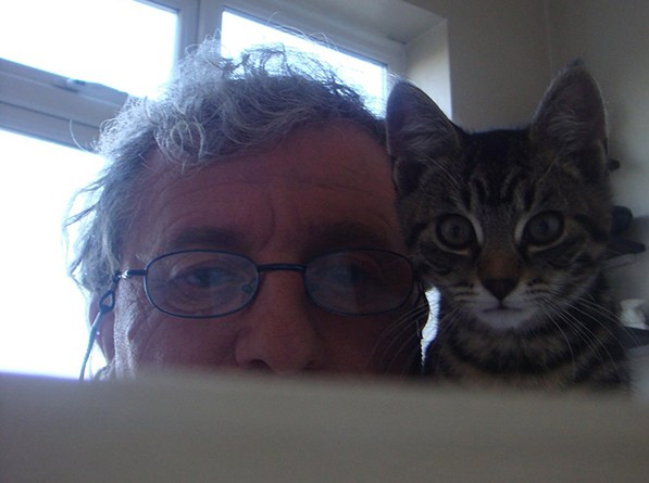 A photo of Martin Pallot and his kitten peeking over a sofa
