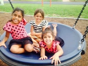 Aboriginal girls playing on a swing