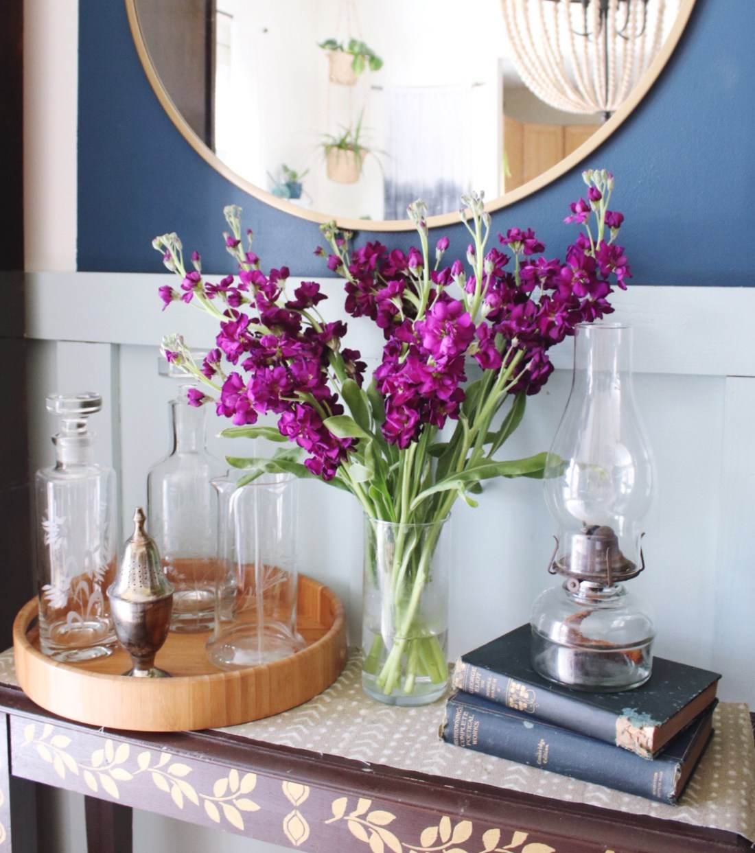 purple spring flowers in vase on a table in front of a large gold mirror