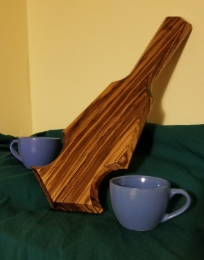 The Verona sitting with the handle up with one blue teacup on each side on top of a green cloth backdrop.