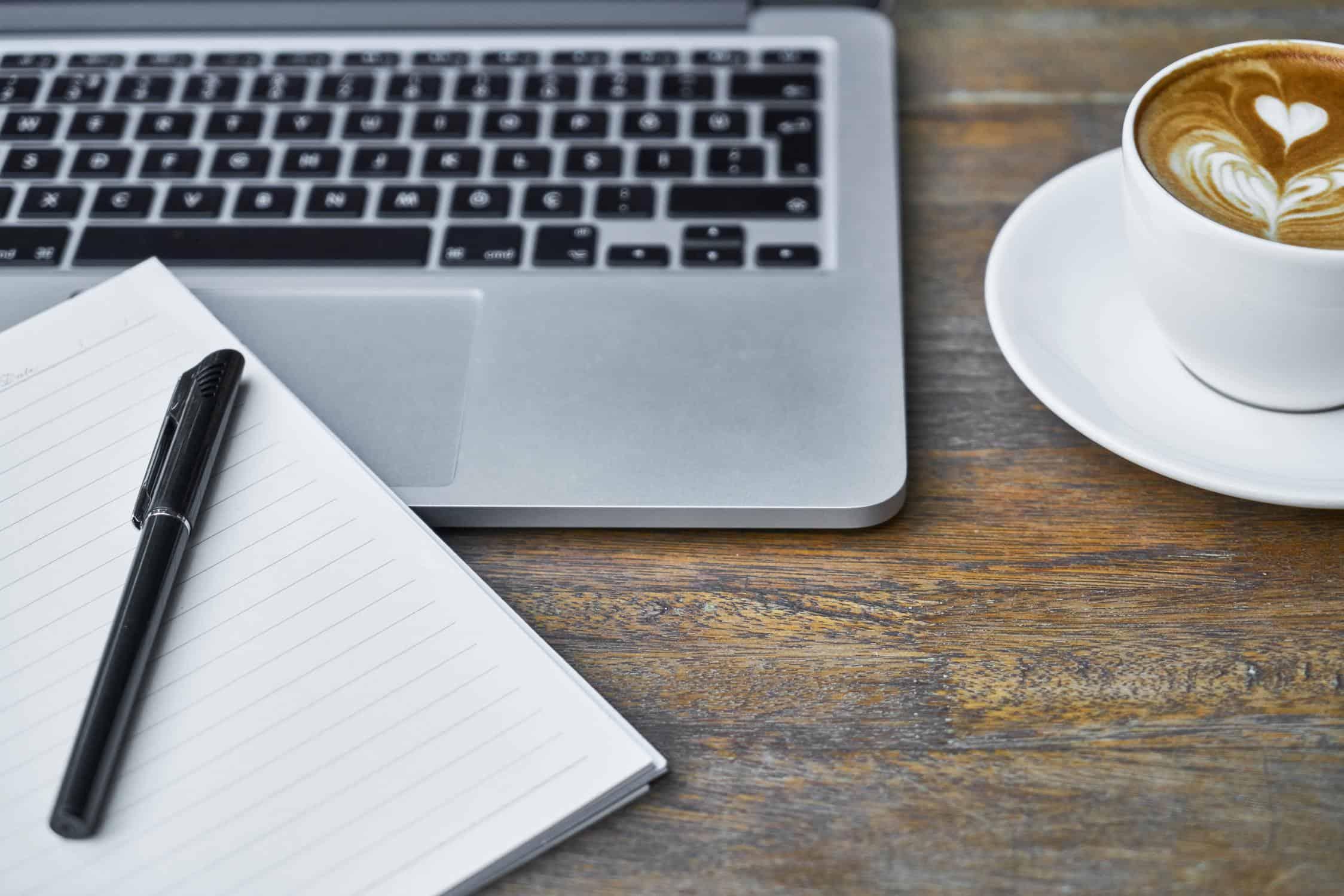 Hidden WordPress Gutenberg Features Header Image Of Notepad Coffee Cup And Laptop On Dark Wood