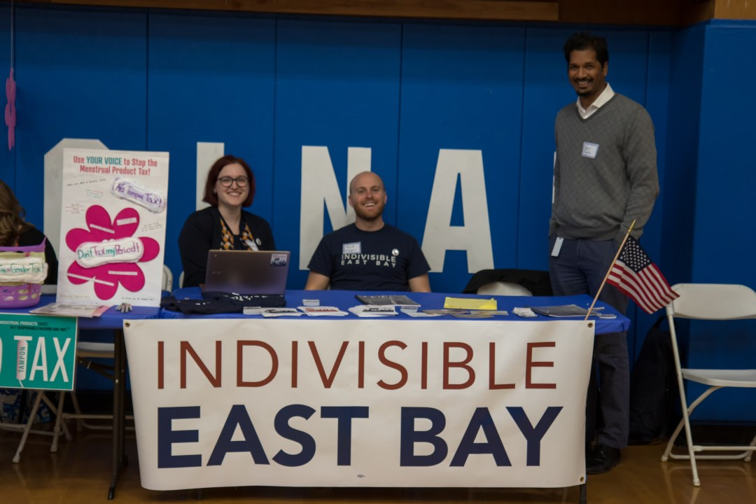 Heather, Nick, and Rohit smiling behind a table with an Indivisible East Bay banner strung across the front.