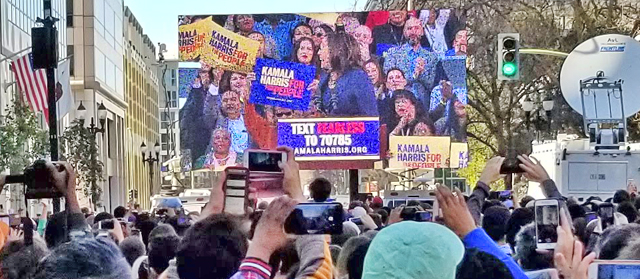 Crowd on 14th street waiting for Kamala Harris with view of video showing crowd in plaza, photo by Jonathan Zingman