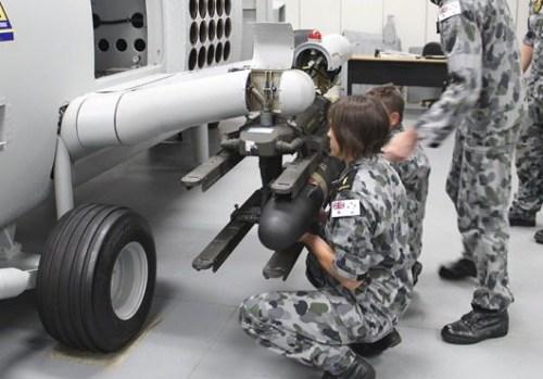 Personel AL Australia tampak mempersiapkan rudal Hellfire pada MH-60R.
