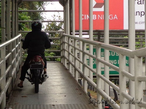 sepeda motor naik jembatan busway