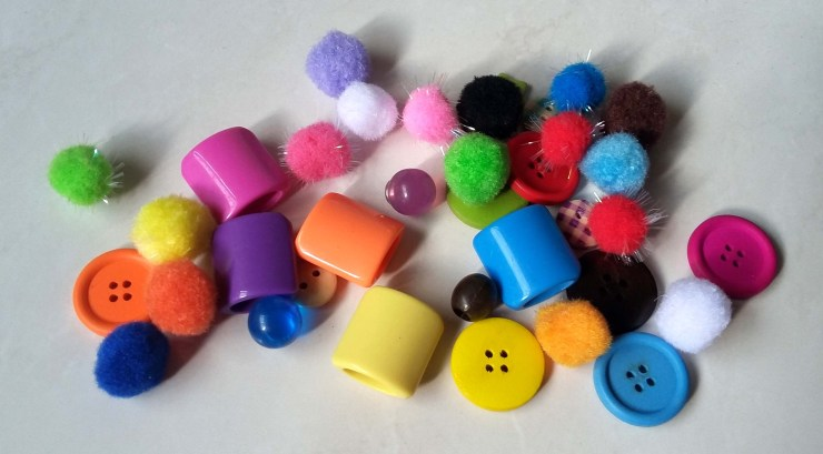 Assortment of buttons, pompoms and beads for a sorting tray toy