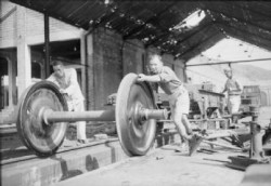 Leading Aircraftman L Moulden, a former blacksmith, helps roll a newly repaired bogey unit for a carriage or flatbed truck into place at the Kowloon Railway's repair sheds, Hong Kong. This railway was immobilised during the Japanese occupation, services were restored under Royal Air Force supervision after the liberation.Made by: Royal Air Force official photographer