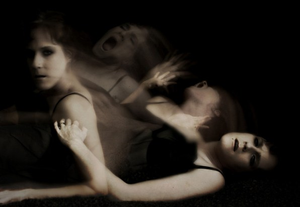 A black and white stop motion photo showing a woman rising from the floor in several stages with a troubled expression on her face.