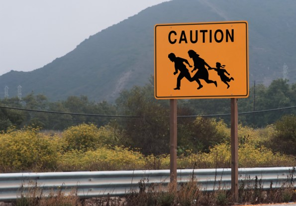 "A sign at the side of a rural highway reads ""Caution"" families of undocumented workers may appear in road."