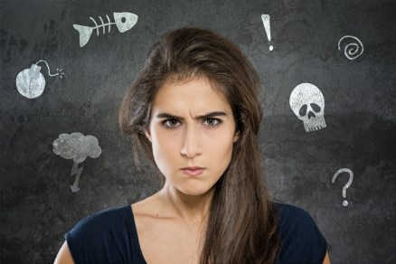 A visibly grumpy young woman is surrounded by illustrations of bones, bombs, and exclamation points.