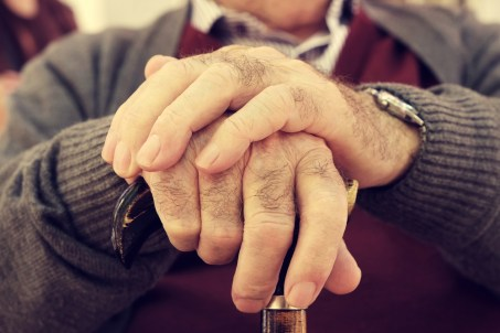 A closeup of an old man's hands as they rest on a walking stick.
