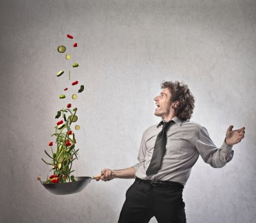 A man in business attire tosses veggies from a pan high into the air.