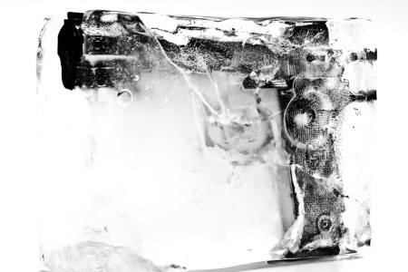 A photo of a handgun frozen in a block of ice.