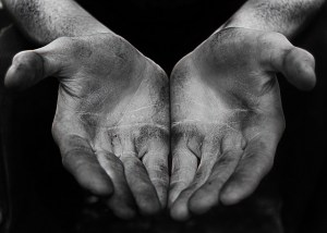 A pair of dirty hands held out in anticipation of food or money.