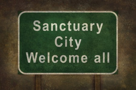 "A photo of a road sign that says, ""sanctuary city, welcome all."""