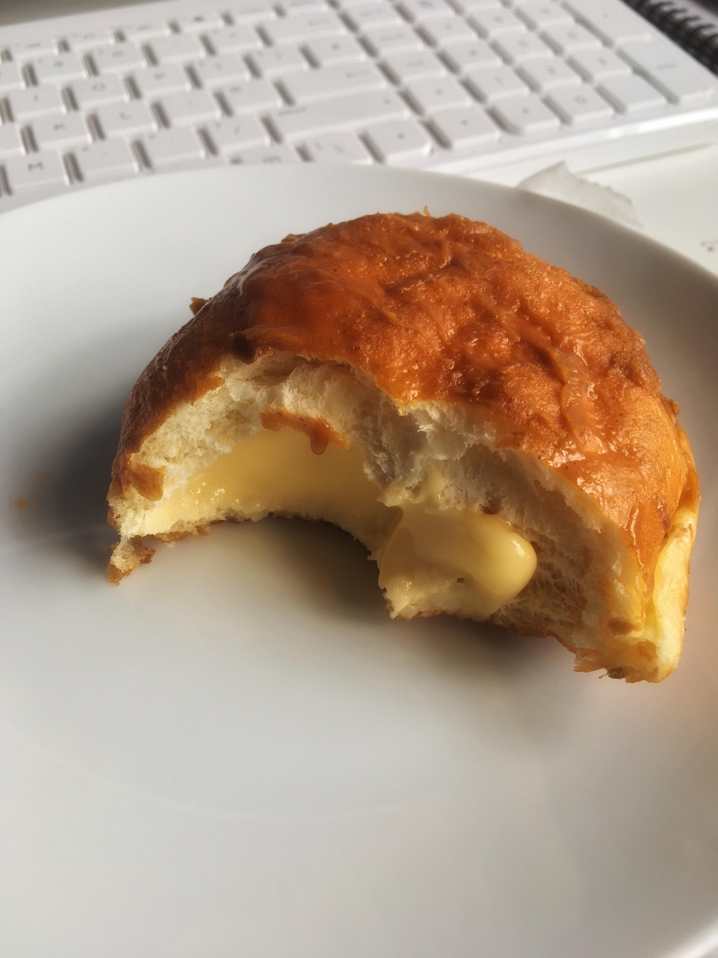 Greggs caramel custard donut, half bitten showing the rich creamy custard centre