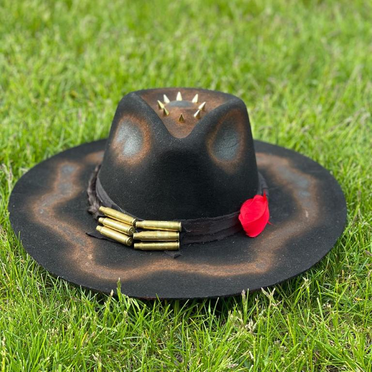 Black custom hat with red feathers and studs in grass